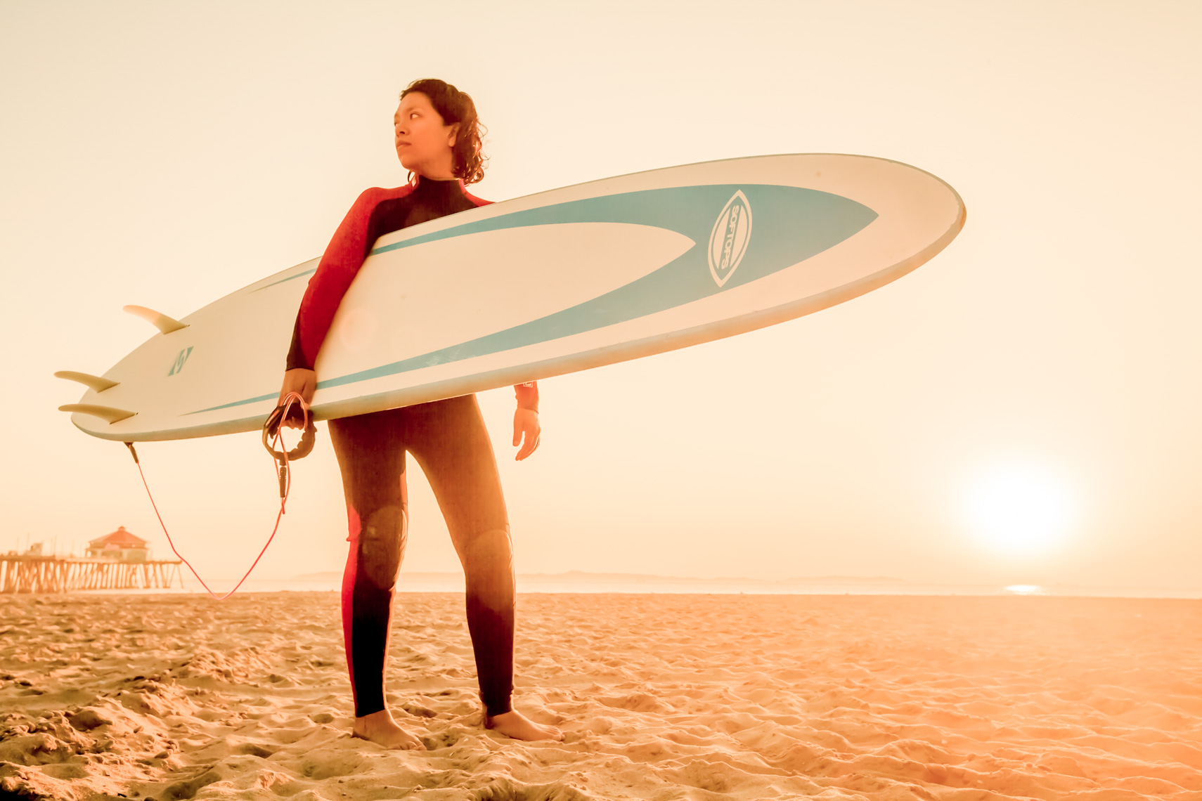 Surfer poses at sunset with surfboard at Huntington Beach, California.